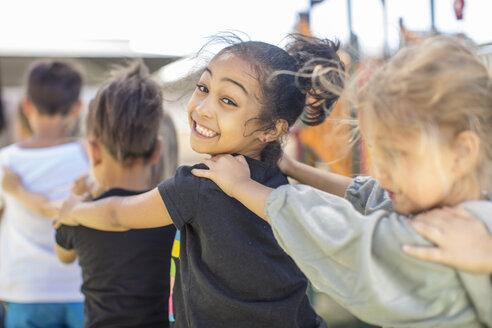 Happy children making a conga line in kindergarten - ZEF15477
