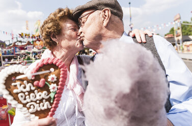Senior couple with gingerbread heart and cotton candy kissing on fair - UUF13739