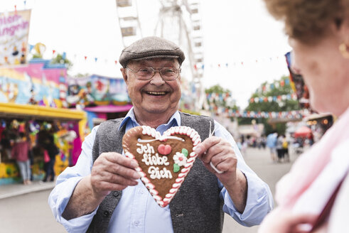 Portrait of happy senior man presenting gingerbread heart on fair - UUF13742