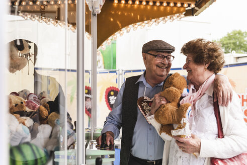 Happy senior couple with prize on fair - UUF13748