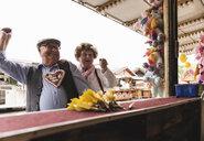 Senior couple having fun on fair - UUF13751