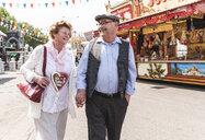 Happy senior couple walking hand in hand on fair - UUF13757