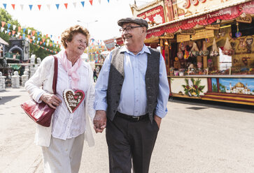 Happy senior couple walking hand in hand on fair - UUF13757