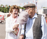 Senior couple on fair enjoying cotton candy - UUF13760