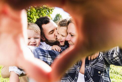 Happy family behind finger frame - UUF13763
