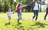 Active happy family walking hand in hand in a park - UUF13772