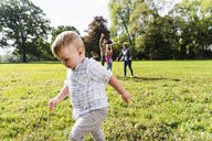 Boy walking in a park with family in background - UUF13775