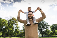Happy father carrying son on shoulders in a park - UUF13781