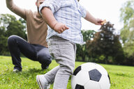 Happy father playing football with son in a park - UUF13784