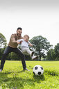Happy father playing football with son in a park - UUF13787