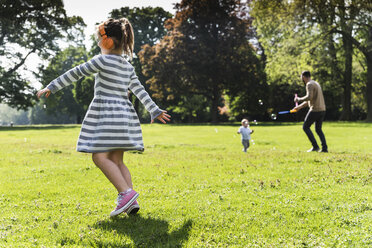 Girl with family wearing headphones in a park - UUF13799