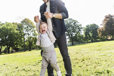 Father holding hands of happy son in a park - UUF13805