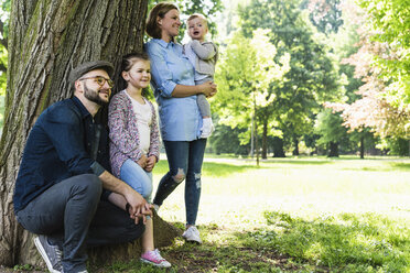 Happy family under a tree in a park - UUF13814