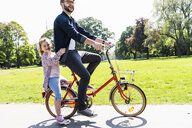 Happy father riding bicycle with daughter in a park - UUF13817