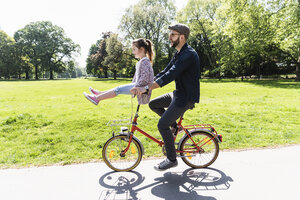 Happy father riding bicycle with daughter sitting on handlebar in a park - UUF13820
