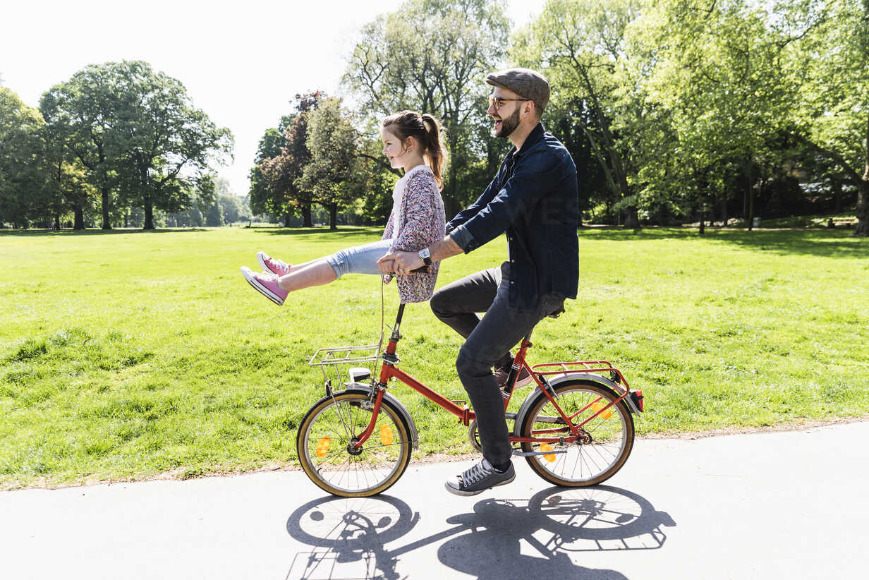 Happy father riding bicycle with daughter sitting on handlebar in a park - UUF13820 - Uwe Umstätter/Westend61