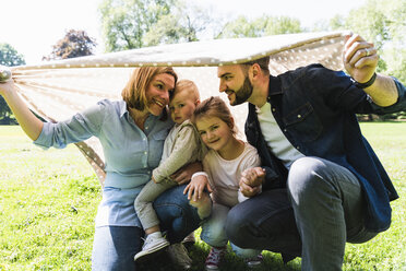 Happy family under a blanket in a park - UUF13823