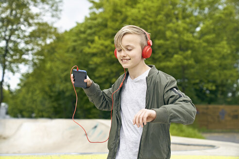 Boy with headphone dancing while listing to music on smartphone - PDF01637