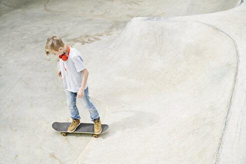Boy with headphones on skateboard, skateboarding - PDF01640