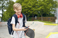 Boy with headphones, skateboard and school bag using smartphone - PDF01643