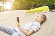 Boy using smartphone in skatepark - PDF01646