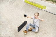 Boy with skateboard taking selfies with smartphone - PDF01649