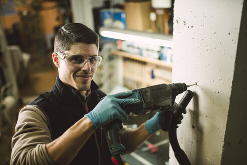 Portrait of smiling man making a hole in the wall with a drill - RAEF02038