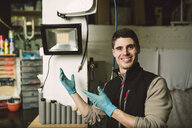 Portrait of a smiling mechanic in his workshop - RAEF02044