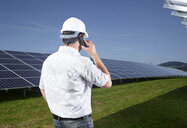 Back view of engineer on the phone in front of solar plant - CVF00541
