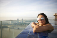 Woman in infinity pool wearing sunglasses, Bangkok, Krung Thep, Thailand, Asia - CUF09274