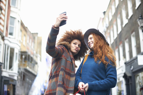 Two young women in street, taking selfie, using smartphone, low angle view - CUF09283