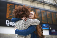 Two young women hugging at train station - CUF09286