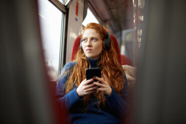 Woman on train listening to music on mobile phone with headphones, London - CUF09292
