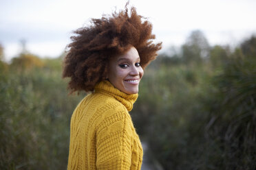 Portrait of woman with afro looking over shoulder at camera smiling - CUF09298