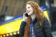 Young woman at train station, talking on smartphone - CUF09304