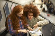 Two young women on escalator, looking at map, elevated view - CUF09307