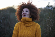 Young woman in rural setting, looking up with excited expression - CUF09334