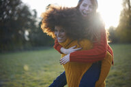 Two young women, in rural setting, young woman giving friend piggyback ride - CUF09337
