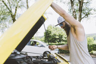 Young male hipster lifting car hood on road trip, Como, Lombardy, Italy - CUF09343