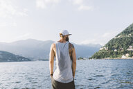 Rear view of young male hipster looking out from waterfront, Lake Como, Lombardy, Italy - CUF09376