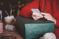 Woman with christmas present using smartphone - CUF09631