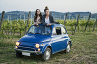 Tourists standing through car sunroof, vineyard, Tuscany, Italy - CUF09685