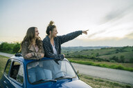 Tourists standing through car sunroof, countryside, Tuscany, Italy - CUF09688