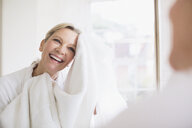 Smiling mature woman drying face with towel at bathroom mirror - HOXF03522