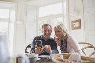 Smiling mature couple using smart phone at dining table - HOXF03555