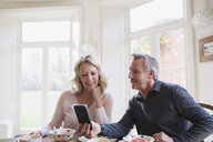 Mature couple using smart phone at breakfast table - HOXF03558