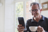 Smiling mature man drinking tea and using smart phone - HOXF03603
