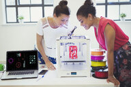 Female designers watching 3D printer in office - CAIF20574
