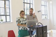 Designers using laptop at 3D printer in office - CAIF20616