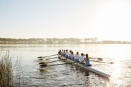 Female rowing team rowing scull on sunny lake - CAIF20646
